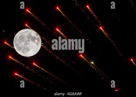 London, UK. 4th November, 2017. 04.11.17. Fireworks streak across the full moon over London for bonfire night celebrations. - Stock Photo