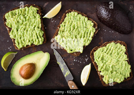 Healthy avocado toast. Mashed avocado on whole grain rye bread on dark background. Top view vegan food - Stock Photo