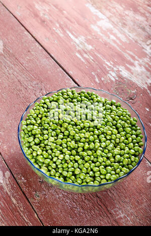 young peas in a clay plate on an old wooden table. Vertical photo with space for text - Stock Photo