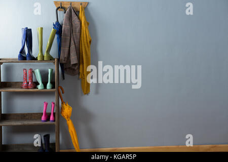 Wellington boots, umbrella and blazer on hook against wall - Stock Photo