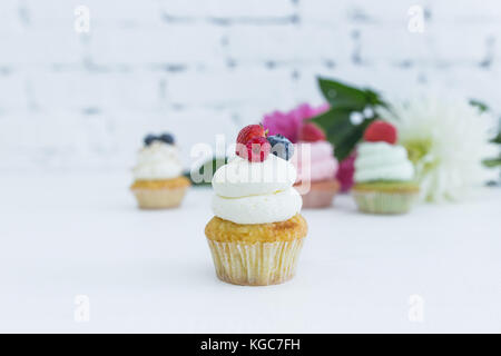 Various cupcakes with fresh berries flowers and leaves. White background. - Stock Photo