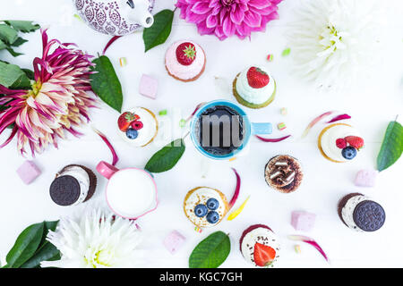 Various cupcakes with fresh berries flowers and leaves, a cup of tea or coffee and a kettle. Top view. White background. - Stock Photo