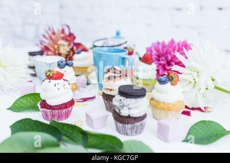 Various cupcakes with fresh berries flowers and leaves, a cup of tea or coffee. White background. - Stock Photo