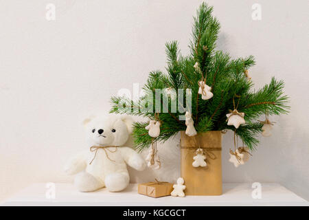 Christmas pine branch in vase with homemade cookies white bear. decor in Scandinavian style, white background. - Stock Photo