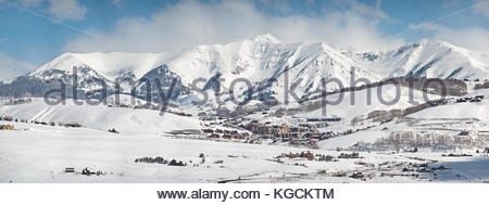 Snow covered Whiterock Mountain towers over the town of Mt. Crested Butte, Colorado on a winter morning. - Stock Photo