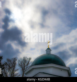 Golden cross on  the dome of a Christian Orthodox church against the stormy spring or winter sky with sun behind - Stock Photo