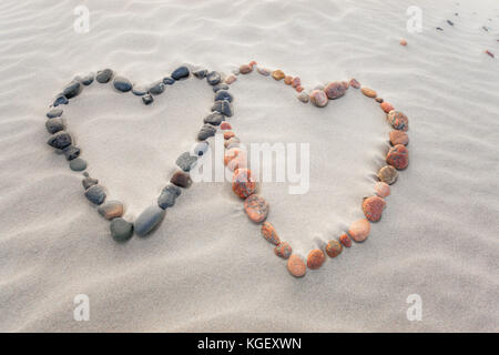 Pebbles arranged in shape of two hearts on sand beach ripples - Stock Photo