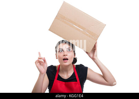 Female employee with cardbox pointing an idea for product storage in the store - Stock Photo