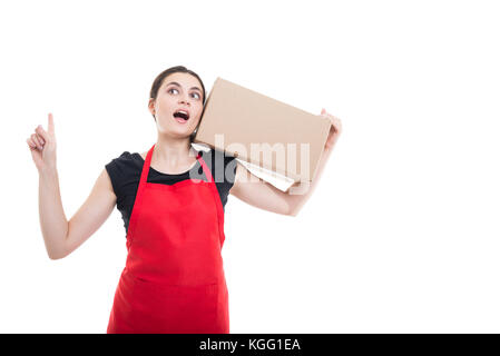 Female seller carrying delivery box in the store and pointing finger up on white background - Stock Photo