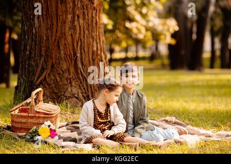 children on picnic blanket - Stock Photo