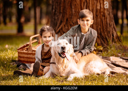Children petting dog in park - Stock Photo