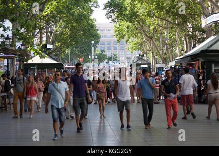 Spain, Barcelona, people walking along La Rambla. - Stock Photo