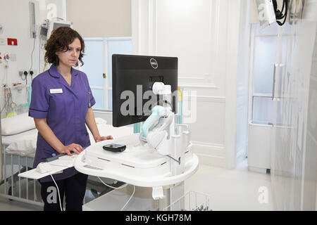 A Nurse checking information on a computer in a hospital. - Stock Photo