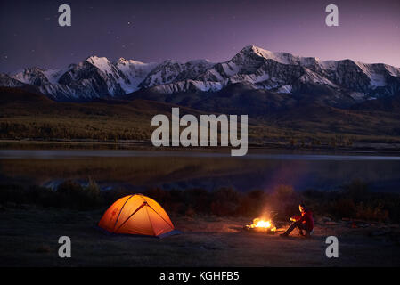 Night camping. Man tourists sitting in the illuminated tent near campfire under amazing sunset evening sky in a - Stock Photo