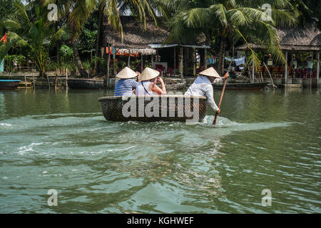 Tourists enjoying tour in traditional coracle boats on river Thu Bon near  Hoi An, Vietnam, south East Asia. - Stock Photo