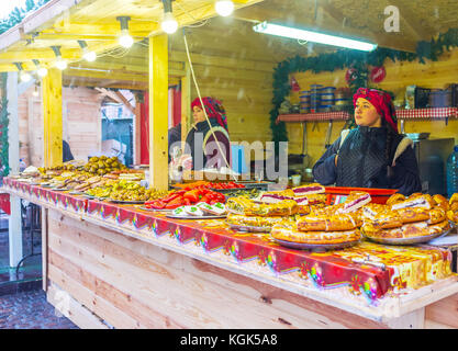 KIEV, UKRAINE - JANUARY 4, 2017: The young sellers offer variety of traditional ukrainian food at Christmas Festival, - Stock Photo