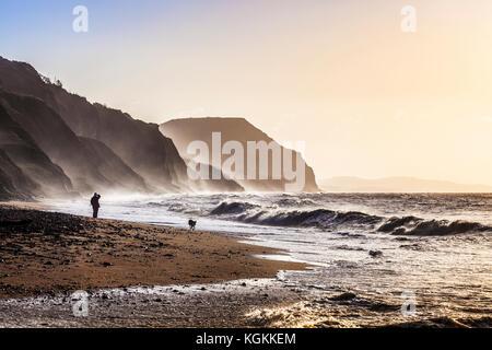 Sunrise on Charmouth beach looking towards Golden Cap. - Stock Photo