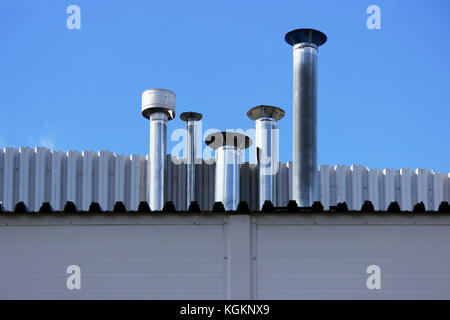 Five chimney pipe from stainless steel on the roof of the house. - Stock Photo