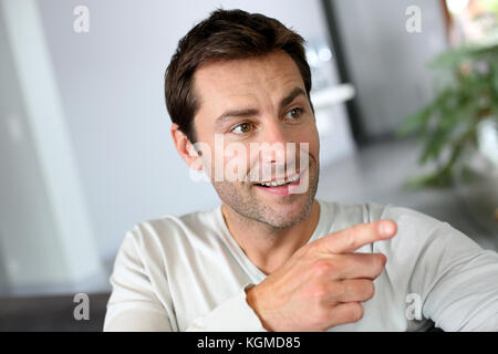 Portrait of man showing something with finger - Stock Photo