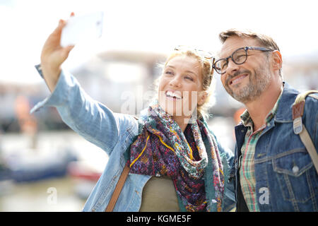 Couple of tourists on vacation taking selfie picture with smartphone - Stock Photo