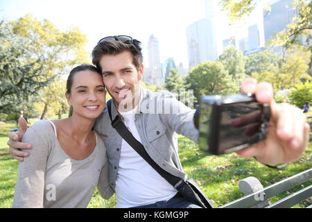 Couple in Central Park taking picture of themselves - Stock Photo