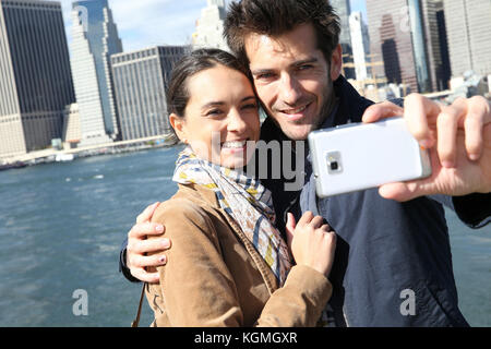 Couple taking picture with Manhattan skyline in background - Stock Photo