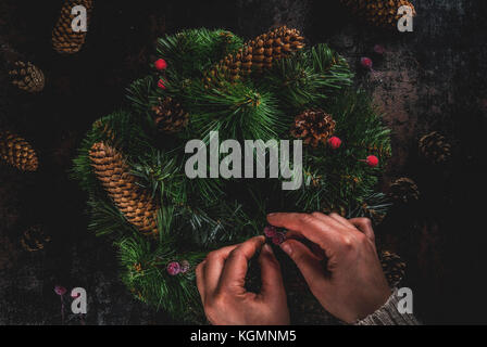 Preparation for xmas holidays. Woman decorating christmas green wreath with pine cones and red winter berries, on - Stock Photo