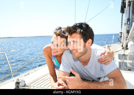Couple relaxing on sailboat deck - Stock Photo