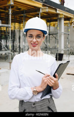 engineer in hardhat holding clipboard - Stock Photo