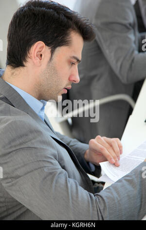 Young man filling in application form - Stock Photo
