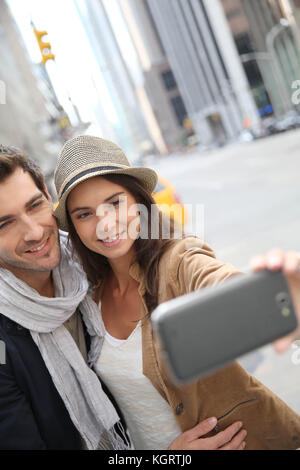 Couple in Manhattan taking picture with smartphone - Stock Photo