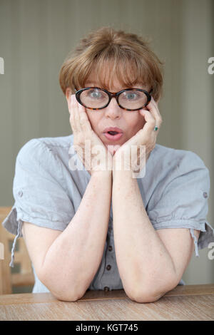Senior woman with surprised look - Stock Photo