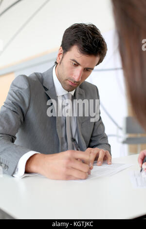 Businessman filling in business contract - Stock Photo