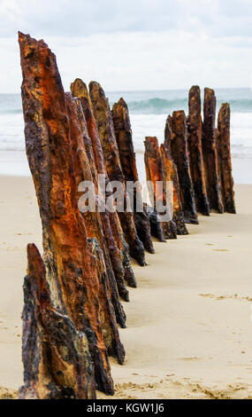 rusty remains of a ships structure on a deserted beach - Stock Photo