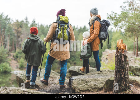 parents and kids trekking in forest - Stock Photo
