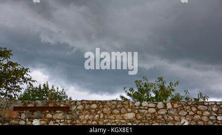 Late summer storm clouds gathering over the walls of a old derelict farmhouse in the region of Friuli in north east - Stock Photo