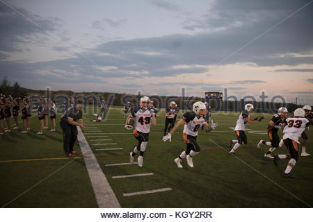 Teenage boy high school football players running, playing game on football field - Stock Photo