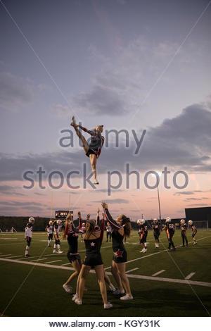 Teenage girl high school cheerleading team cheering, jumping on sideline of game on football field - Stock Photo