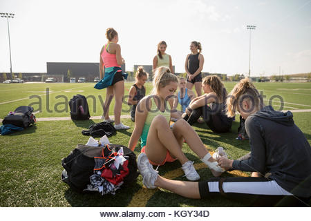 Teenage girl high school cheerleading team taping foot and ankle with tape on sunny football field - Stock Photo
