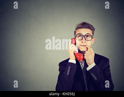 Misunderstanding and distant call. Upset worried confused man talking on a phone has many questions isolated on - Stock Photo