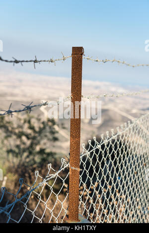 Safety barbed wire fence wuth view of Larnaca bay - Stavrovouni monastery on a mountain peak - Stock Photo