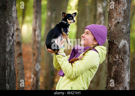 baby girl outdoors with a small dog.smiling teenage girl relaxing with dog.Cute teen girl wearing a jacket and purple - Stock Photo