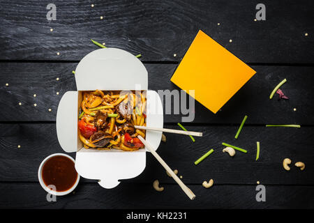 Udon stir fry noodles with meat and vegetables in a box on black background. With chopsticks and sauce. Top view. - Stock Photo