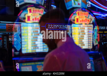 A man plays the slot machines in an amusement arcade in Chinatown in Soho in London's West End, UK - Stock Photo