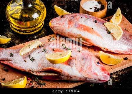 Fresh raw fish pink tilapia with spices for cooking - lemon, salt, pepper, herbs, on  black rusty metal table, copy - Stock Photo