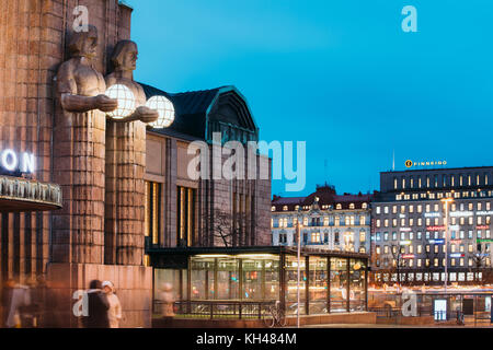 Helsinki, Finland - December 7, 2016: Night View Of Statues On Entrance To Helsinki Central Railway Station And - Stock Photo