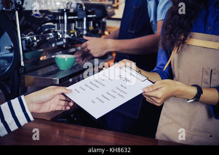 Baristas are recommending coffee menu to customer. Cafe restaurant service, Small business owner, food and drink - Stock Photo