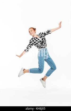 Full length image of carefree ginger woman in shirt and jeans jamping and looking at the camera over white background - Stock Photo