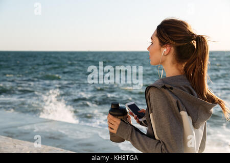 Back view of young brunette sport woman holding bottle of water while listening to music, seaside outdoor - Stock Photo