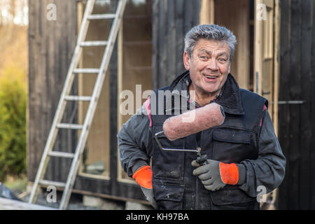 Senior man holding a paint roller smiling in to camera. - Stock Photo